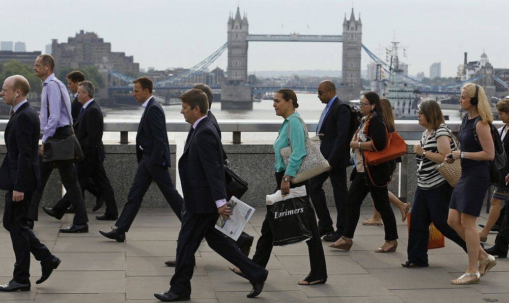 Commuters walk across London Bridge to the City of London August 7, 2013. The Bank of England broke with tradition on Wednesday, saying it planned to keep interest rates at a record low until unemployment falls to 7 percent or below, which it views as unlikely for another three years. REUTERS/Luke MacGregor (BRITAIN - Tags: BUSINESS EMPLOYMENT)