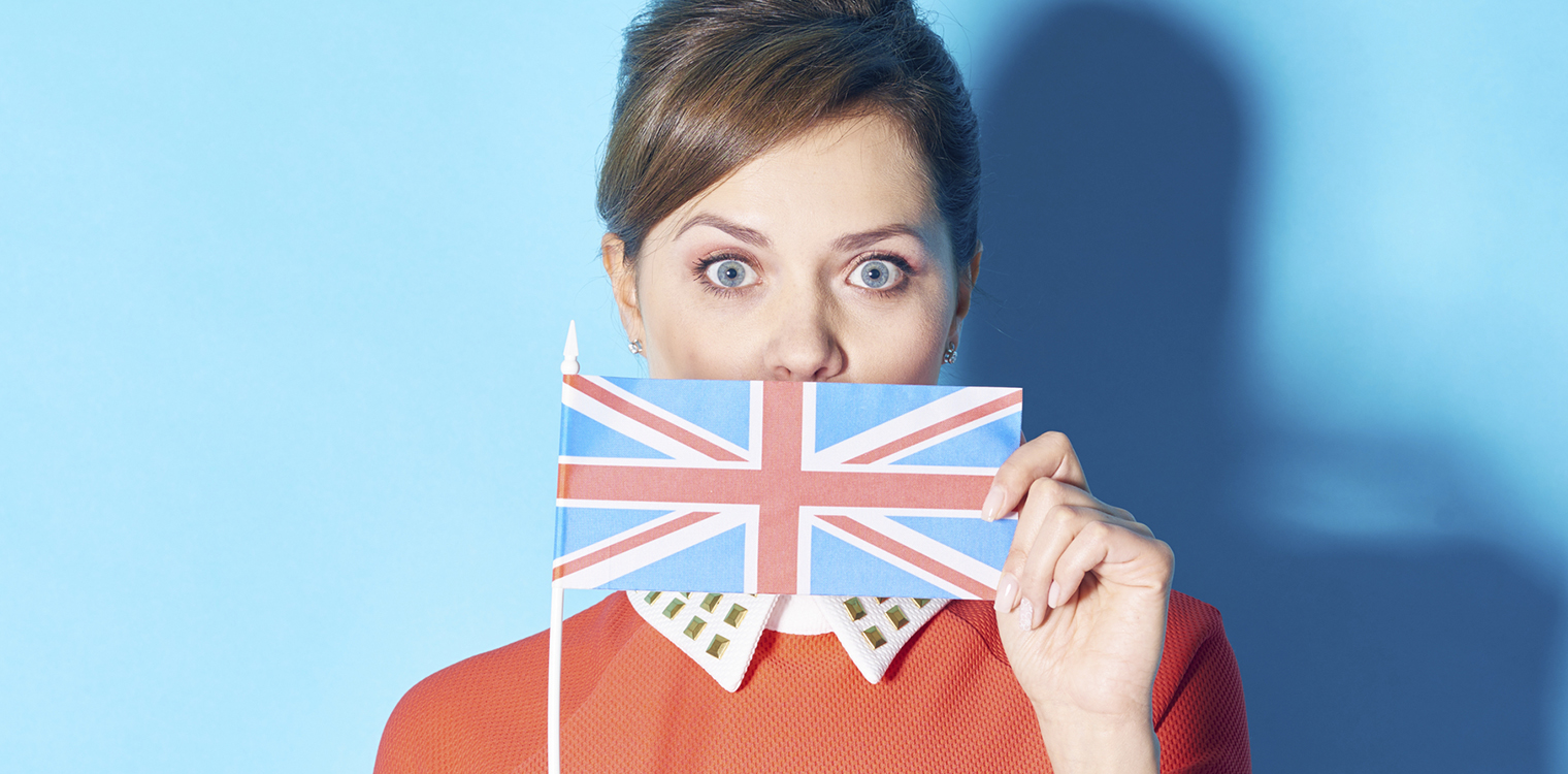 Shocked woman covering her mouth with Britain flag