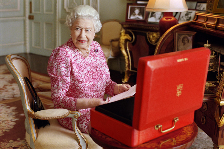 LONDON, UNITED KINGDOM - JULY 2015: (This image is free of charge for a month from release. Use or reproduction in any format on any platform after October 8, 2015, must be approved first by Royal Communications at Buckingham Palace.)  In this handout photo released by Buckingham Palace on September 8, 2015, Queen Elizabeth II is seated at her desk in her private audience room at Buckingham Palace with one of her official red boxes which she has received almost every day of her reign and contain important papers from government ministers in the United Kingdom and her Realms and from her representatives across the Commonwealth and beyond. The photo has been taken by Mary McCartney in July 2015, to mark the moment she becomes the longest reigning British Monarch. (Photo by Mary McCartney/Her Majesty Queen Elizabeth II via Getty Images)