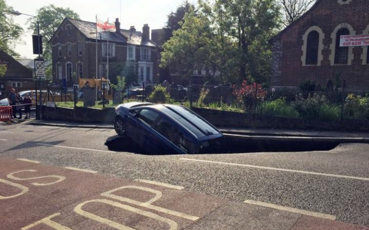 97662597_A_car_which_has_partially_disappeared_down_a_sinkhole_in_Woodland_Terrace_in_Greenwich_sout-large_trans++T1CHodmL3LaIfnPoainGNAb643Od-MrFK7Cuixbkngg