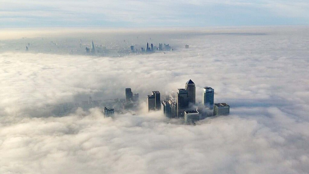 The Canary Wharf financial district (front) and central London emerge from morning fog in this aerial photograph released by the Metropolitan Police in London March 13, 2014. REUTERS/Metropolitan Police/Handout via Reuters (BRITAIN - Tags: BUSINESS CITYSCAPE ENVIRONMENT TPX IMAGES OF THE DAY) ATTENTION EDITORS - THIS IMAGE WAS PROVIDED BY A THIRD PARTY. FOR EDITORIAL USE ONLY. NOT FOR SALE FOR MARKETING OR ADVERTISING CAMPAIGNS. THIS PICTURE IS DISTRIBUTED EXACTLY AS RECEIVED BY REUTERS, AS A SERVICE TO CLIENTS. NO COMMERCIAL OR BOOK SALES. NO SALES. NO ARCHIVES. NO THIRD PARTY SALES. NOT FOR USE BY REUTERS THIRD PARTY DISTRIBUTORS