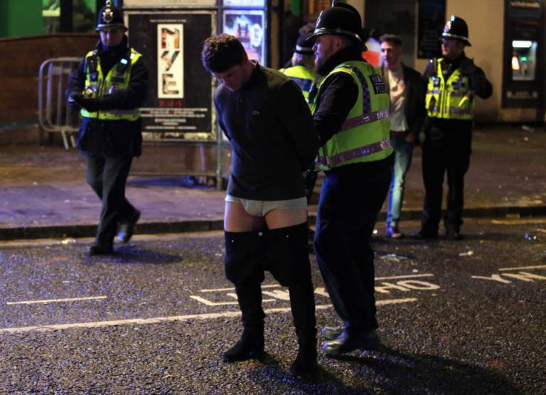 Pictured: A man whose trousers are falling down is detained by police officers Friday 01 January 2016  Re: New Year revellers in Wind Street, Swansea, south Wales.