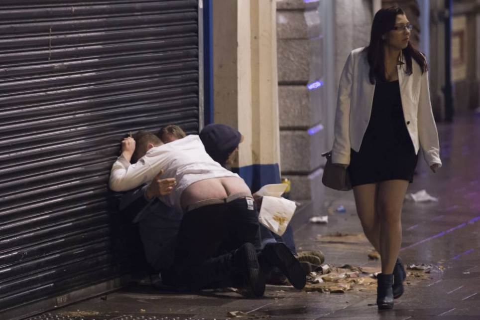 Revellers out in Cardiff, South Wales, celebrating New Year's Eve. Police increased patrols in the city centre in an attempt to crack down on alcohol-related disorder. Picture shows a man with his trousers down on St. Mary's Street, Cardiff. PIC Matthew Horwood © WALES NEWS SERVICE