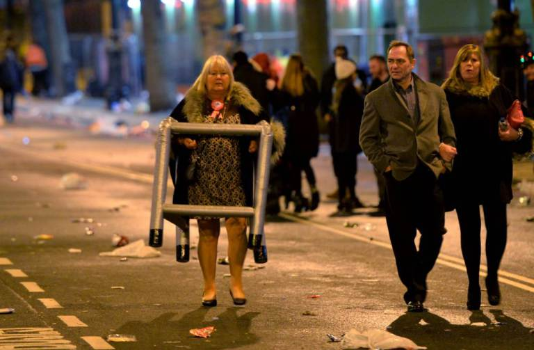 Revellers head home as the clean-up begins in central London after the New Year celebration fireworks. PRESS ASSOCIATION Photo. Picture date: Friday January 1, 2016. Photo credit should read: Anthony Devlin/PA Wire