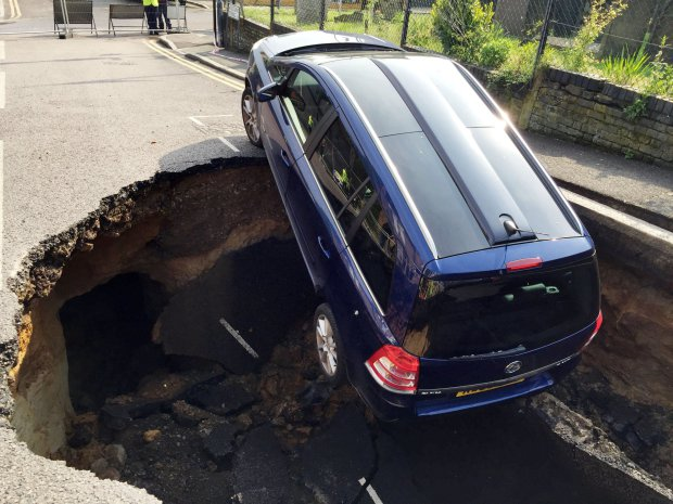 A car which has partially disappeared down a sinkhole in Woodland Terrace in Greenwich, south-east London. PRESS ASSOCIATION Photo. Picture date: Thursday May 12, 2016. See PA story POLICE Sinkhole. Photo credit should read: Joe Nerssessian/PA Wire