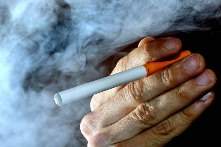 """A person smokes an electronic cigarette, or e-cigarette.  Electronic cigarettes are to be classed as """"medicines"""" under new proposals to tighten up the regulation of nicotine-containing products. Manufacturers are to face tough new tests before they can sell their e-cigarettes as """"licensed products"""", the Medicines and Healthcare products Regulatory Agency (MHRA) said."""