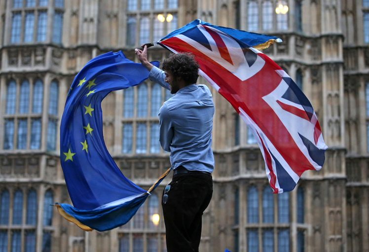 A man waves both a Union flag and a European flag together on College Green outside The Houses of Parliament at an anti-Brexit protest in central London on June 28, 2016. EU leaders attempted to rescue the European project and Prime Minister David Cameron sought to calm fears over Britain's vote to leave the bloc as ratings agencies downgraded the country. Britain has been pitched into uncertainty by the June 23 referendum result, with Cameron announcing his resignation, the economy facing a string of shocks and Scotland making a fresh threat to break away. / AFP / JUSTIN TALLIS (Photo credit should read JUSTIN TALLIS/AFP/Getty Images)