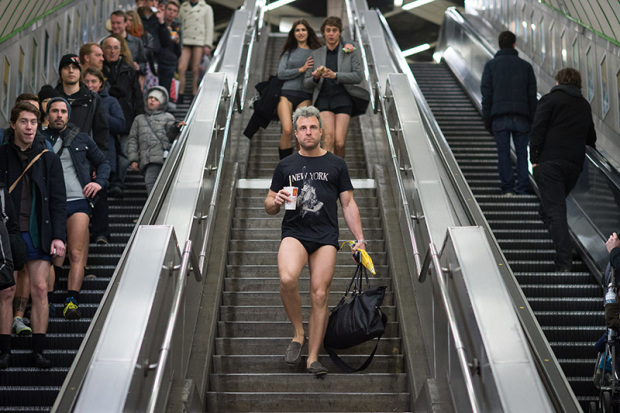"""People walk down stairs and take escalators as they take part in the annual """"No Trousers On The Tube Day"""" event in central London on January 11, 2015. Originally started in the US, the international event, also known as the """"No Pants Subway Ride"""" was created by improvisation group """"Improv Everywhere"""" and sees people taking train journies while wearing no trousers, yet acting as normally as possible. AFP PHOTO / LEON NEAL (Photo credit should read LEON NEAL/AFP/Getty Images)"""
