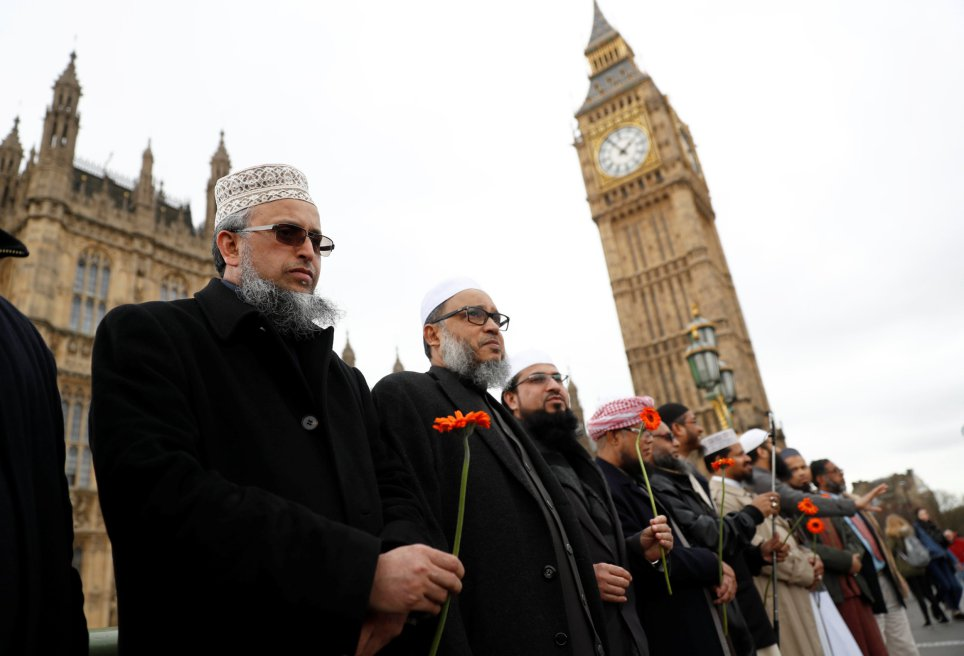 Muslim men hold flowers as they stand in line on Westminster Bridge during an event to mark one week since a man drove his car into pedestrians then stabbed a police officer in London, Britain, March 29, 2017. REUTERS/Stefan Wermuth