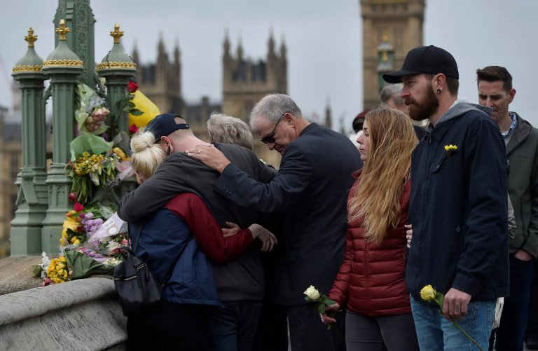 People embrace after laying flowers during an event to mark one week since a man drove his car into pedestrians on Westminster Bridge then stabbed a police officer in London, Britain March 29, 2017. REUTERS/Hannah McKay